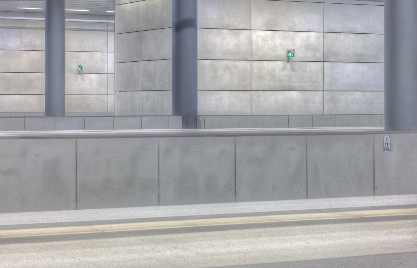 Hellgraue Wände mit Stützen in einem Bahnhof